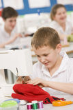 Junge, der eine Nähmaschine verwendet Lizenzfreies Stockfoto