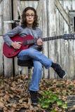Junge, der eine rote Gitarre spielt Lizenzfreies Stockbild