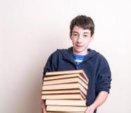 Junge, der eine schwere Eingabe der Bücher trägt Lizenzfreie Stockfotografie