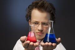 Junge, der eine Substanz in einer Retorte studiert stockfotos