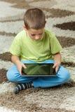 Junge, der eine Tablette verwendet Lizenzfreies Stockfoto