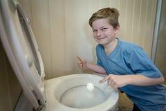 Junge, der eine Toilette mit Plastik als Streich umfasst Lizenzfreie Stockfotos