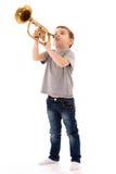 Junge, der in eine Trompete durchbrennt stockfoto