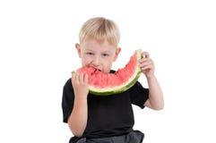 Junge, der eine Wassermelone isst Lizenzfreie Stockbilder