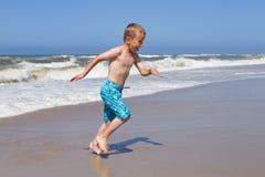 Junge, der eine Welle am sandigen Strand flieht Lizenzfreie Stockfotos