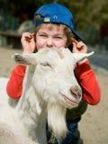 Junge, der eine Ziege umarmt Stockbilder
