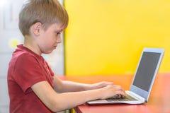 Junge, der an einem Laptop arbeitet Stockfoto