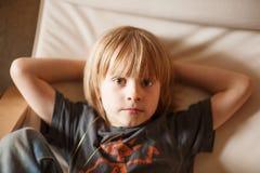 Junge, der in einem Lehnsessel stillsteht Lizenzfreie Stockbilder