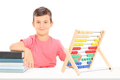 Junge, der an einem Schreibtisch mit einem Abakus und Büchern auf ihm sitzt Lizenzfreie Stockfotografie