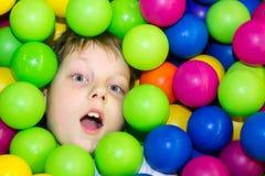 Junge, der in einem Stapel von farbigen Bällen liegt Stockfotografie
