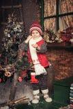 Junge, der in einem Weihnachtsgarten spielt Lizenzfreies Stockbild