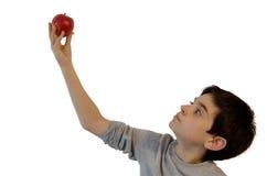 Junge, der einen Apfel anhält Lizenzfreie Stockfotografie