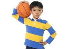 Junge, der einen Basketball anhält Lizenzfreies Stockbild