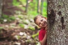 Junge, der einen Baum im Wald umarmt Lizenzfreies Stockbild