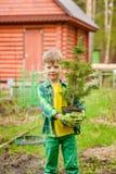 Junge, der einen Baumsämling in den Händen hält stockfotos