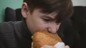 Junge, der einen Burger in einem Restaurant isst Der Junge hält einen Hamburger mit Rindfleisch stock video
