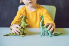 Junge, der einen Dinosaurier als Paläontologe zeigt Stockfotografie