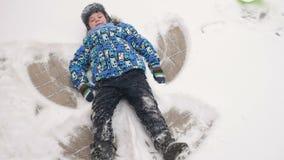 Junge, der einen Engel auf dem Schnee tut stock video