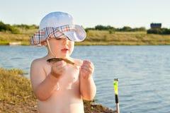 Junge, der einen Fisch anhält Lizenzfreie Stockfotografie