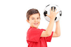 Junge, der einen Fußball hält und Kamera betrachtet Lizenzfreies Stockfoto