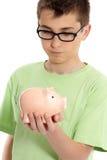 Junge, der einen Geldkasten der piggy Querneigung anhält Stockfotografie
