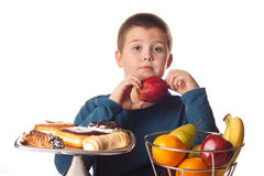 Junge, der einen gesunden Apfel wählt Stockbild