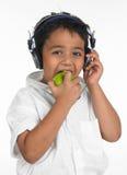 Junge, der in einen grünen Apfel beißt Stockbilder