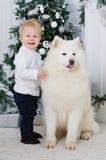 Junge, der einen großen weißen Hund umarmt stockbild
