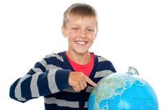 Junge, der einen Kontinent auf der Kugel unterstreicht Lizenzfreie Stockfotografie
