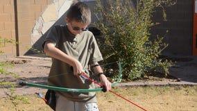 Junge, der einen Pfeil und Bogen schießt stock video footage