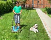 Junge, der einen Rasenmäher durch das Yard drückt -, das von seinem tun Sie begleitet wird lizenzfreie stockbilder