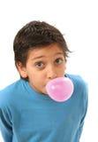 Junge, der einen rosafarbenen Kaugummi durchbrennt Stockbild