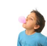 Junge, der einen rosafarbenen Kaugummi durchbrennt Lizenzfreies Stockbild