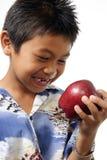 Junge, der einen roten Apfel bewundert lizenzfreies stockbild