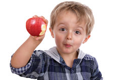 Junge, der einen roten Apfel isst stockfotografie