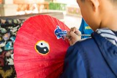 Junge, der einen roten Regenschirm malt Stockfotografie