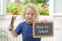 Junge, der einen Schiefer geschrieben zurück zu Schule hält Stockbild