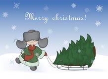 Junge, der einen Schlitten mit einem Weihnachtsbaum zieht Stockbilder