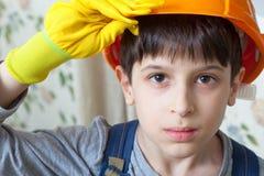 Junge, der einen Schutzhelm und Handschuhe trägt Lizenzfreies Stockfoto