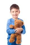 Junge, der einen Teddybären umarmt Lizenzfreie Stockbilder