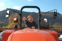 Junge, der einen Traktor antreibt Stockbilder
