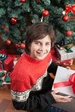 Junge, der einen Weihnachtskasten sitzt im Boden öffnet Stockfotos