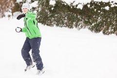 Junge, der einen Winterschneeballkampf genießt Lizenzfreies Stockfoto