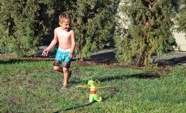 Junge, der in einer Rasenberieselungsanlage spielt Stockfoto