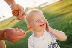 Junge, der Eiscreme, schmutziges Gesicht, grüne Wiese, sonnig isst Stockfotografie