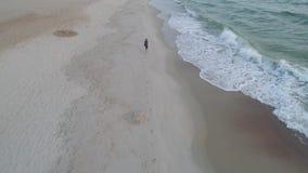 Junge, der entlang den Strand läuft stock video footage