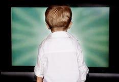 Junge, der entlang des Fernsehbildschirms anstarrt Stockfoto