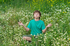 Junge, der in entspannender Haltung sitzt Lizenzfreie Stockfotografie