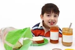 Junge, der Erdnussbutter und Gelee bildet Stockfotografie