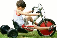 Junge, der erlernt, das Dreirad zu reiten, Lizenzfreie Stockbilder